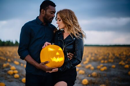 couple standing in pumpkin field and holding scary face pumpkin, concept halloween Banque d'images - 133677275