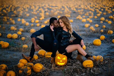 Couple sitting in field near scary face pumpkin, concept halloween Banque d'images - 133677276