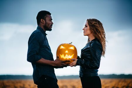 couple standing in pumpkin field and holding scary face pumpkin, concept halloween Banque d'images - 133677278