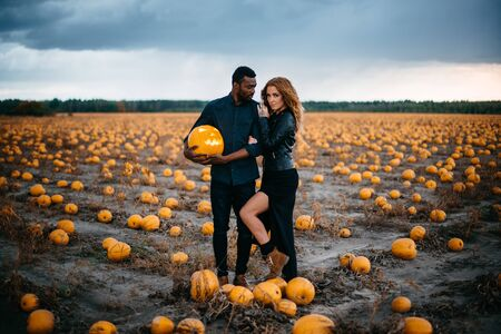 couple standing in pumpkin field and holding scary face pumpkin, concept halloween