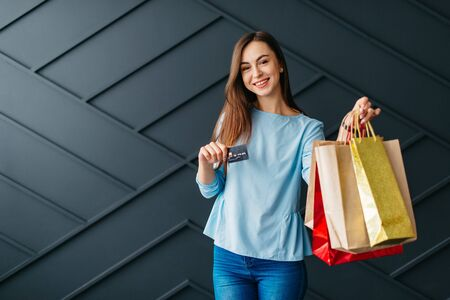 Happy woman holding credit card and bags with purchases, black friday concept Banque d'images - 133677280