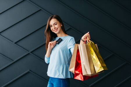 Black friday concept, cheerful woman holding payment card and shopping bags in her hands Banque d'images - 133677281
