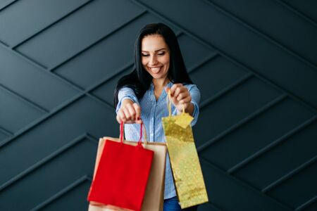 Cheerful woman showing shopping bags, black friday concept Banque d'images - 133677284