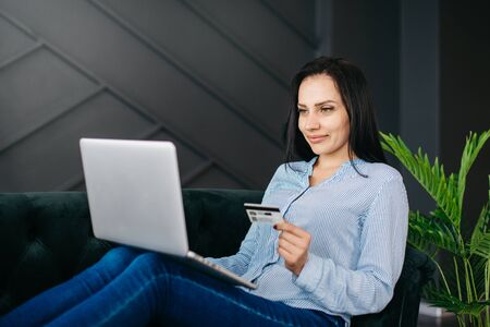 Young woman enters credit card details on laptop for online payment