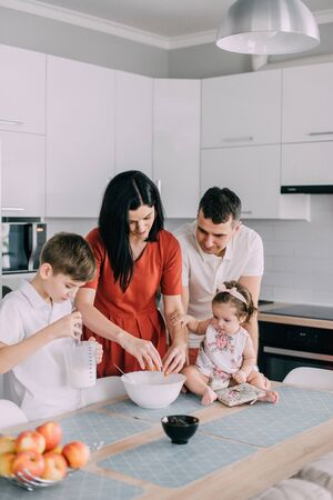 Young family preparing food in kitchen at home