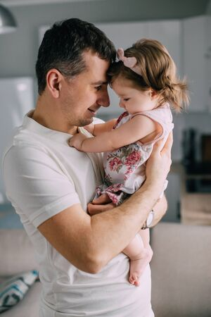 Young father holds on hands little daughter at home, close-up Banque d'images - 133677286