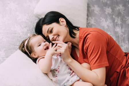 Young mother has fun with her one-year-old daughter in bed, close-up Banque d'images - 133677962