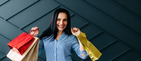 Happy woman holding shopping bags in hands on black background Banque d'images - 133677985