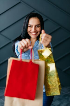 Happy woman holding shopping bags in hands on black background Banque d'images - 133678001