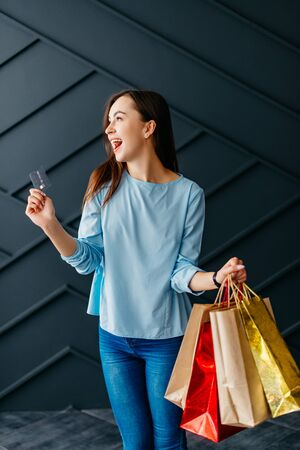Happy woman holding credit card and bags with purchases on black background Banque d'images - 133678015