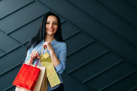 Happy woman holding shopping bags in hands on black background Banque d'images - 133678017