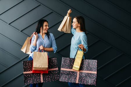 Two cheerful girlfriends rejoice over purchases on black background Banque d'images - 133678084