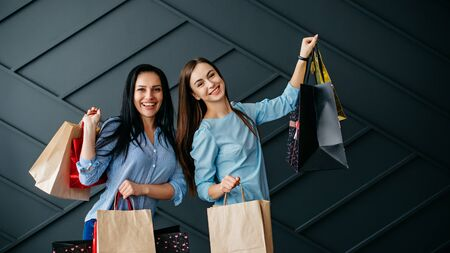Two cheerful girlfriends rejoice over purchases on black background Banque d'images - 133678086