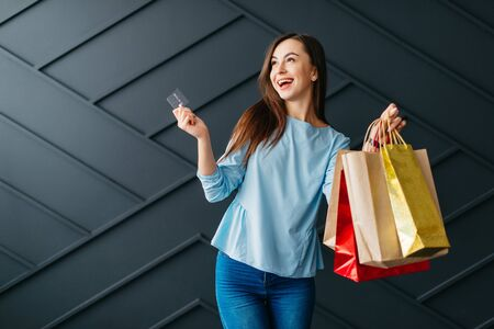 Happy woman holding credit card and bags with purchases on black background Banque d'images - 133678087