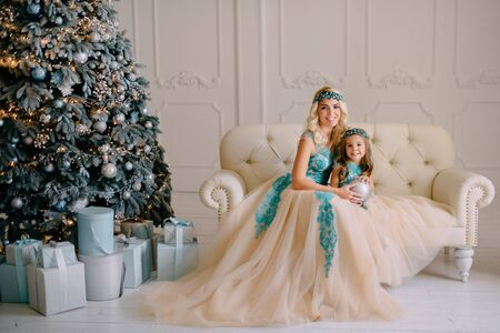 Smiling mom and little daughter in luxurious dresses are sitting on couch Banque d'images - 133678088