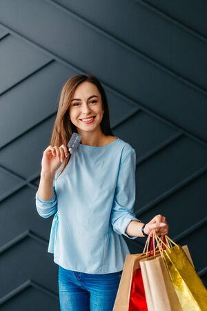 Happy woman holding credit card and bags with purchases, black friday concept Banque d'images - 133678091