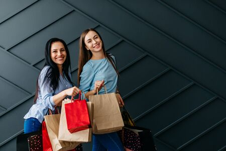 Two cheerful girlfriends holding shopping bags in their hands, black friday concept Banque d'images - 133678092