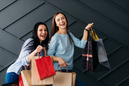 Two cheerful girlfriends holding shopping bags in their hands, black friday concept Banque d'images - 133678093