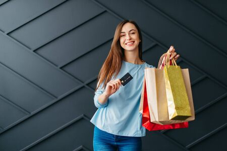 Happy woman holding credit card and bags with purchases, black friday concept Banque d'images - 133678094