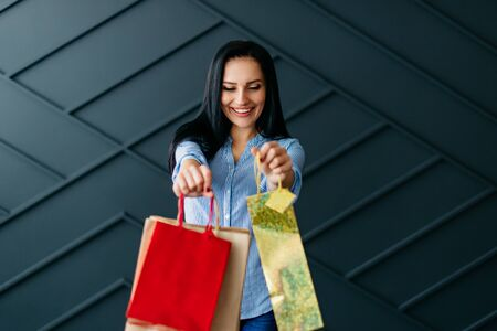 Cheerful woman showing shopping bags, black friday concept Banque d'images - 133678095