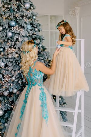 Mom and little daughter in luxurious dresses decorate Christmas tree Banque d'images - 133678242