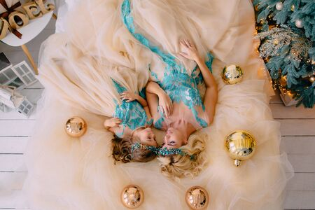 Top down view mom with little daughter in luxurious dresses lie on floor Banque d'images - 133678252