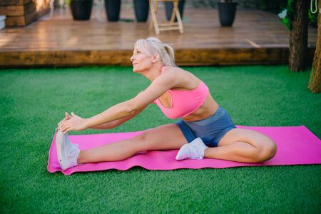 Young athletic woman doing leg muscle stretching on a green lawn, concept of healthy lifestyle