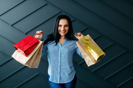 Happy woman holding shopping bags in hands Banque d'images - 133678265
