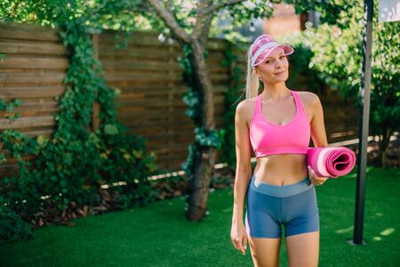 Portrait of young smiling woman with fitness mat Banque d'images - 133678269