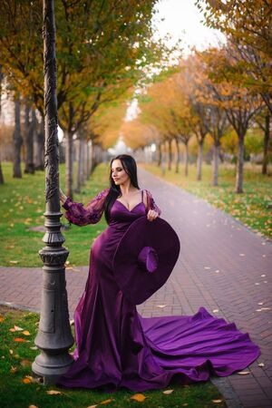 young woman in vintage silk dress is standing in autumn park Banque d'images - 133678354
