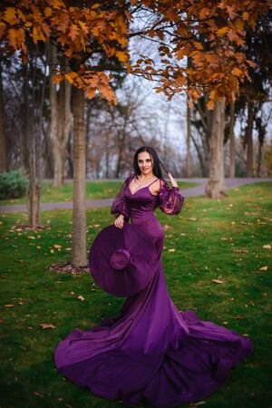 young woman in vintage silk dress is standing in autumn park Banque d'images - 133678357