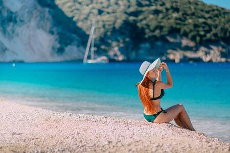 Young happy woman is sitting on beautiful beach Banque d'images - 133678373