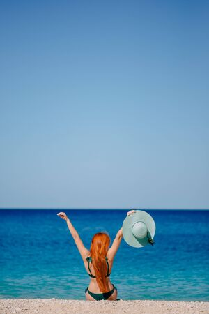 Happy woman enthusiastically raises her hands up sitting on beach, sunny day Banque d'images - 133678408