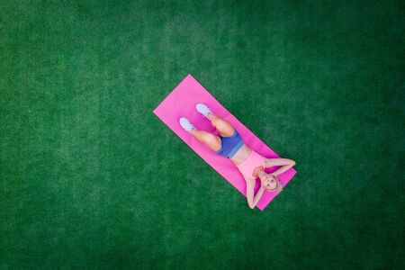 Top view woman doing fitness while lying on green grass on summer day, drone shot Stock Photo