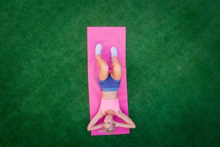 Top view woman doing fitness while lying on green grass on summer day