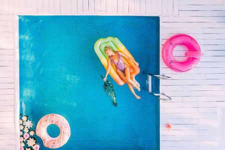 Young female basking in sun while swimming in pool on an air mattress, drone shot