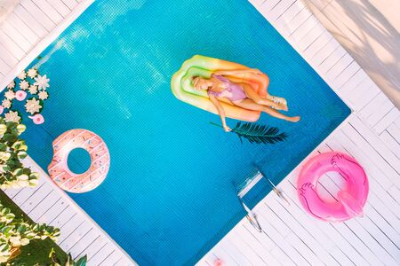 Young female basking in sun while swimming in pool on an air mattress, drone shot 版權商用圖片 - 135524668