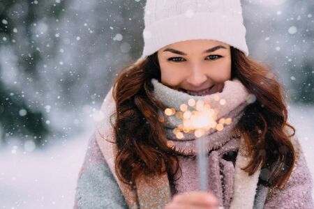 Young smiling woman holding a burning sparkler in her hands, closeup portrait. Banque d'images