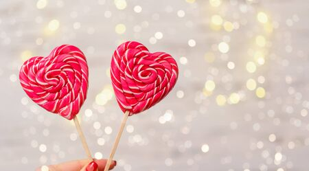 Two colorful candy in the shape of hearts on the background bokeh, close-up. The Concept Of Valentines Day.
