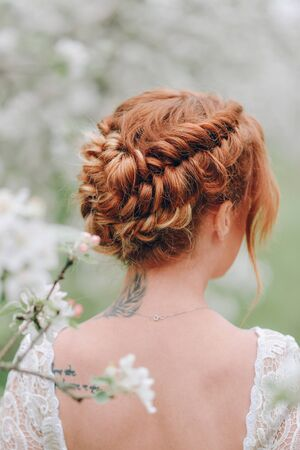 A red-haired woman stands in a flowering spring garden with her back to the camera. Close-up hairstyles. Standard-Bild