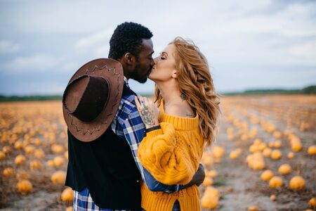 A young interracial couple kisses in a pumpkin field, close-up.