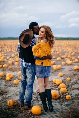 A young couple of farmers stand in a pumpkin field and look at the crop, rear view.