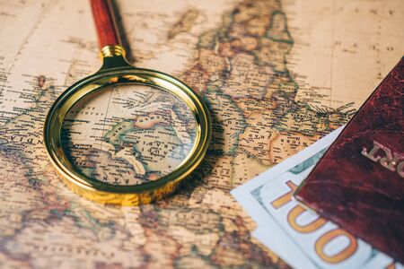 Magnifying glass and passport with money on a vintage world map. View from above.
