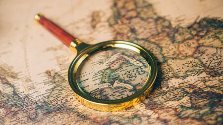 Magnifying glass on a vintage world map. Close up. Stock fotó