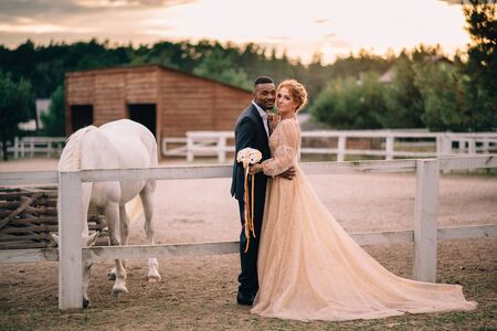 Two lovers black man and white woman stand embracing on a ranch at sunset