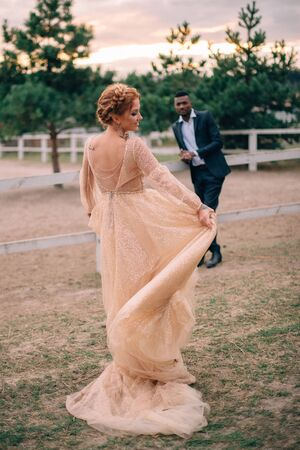 Groom watches his bride spin in front of him at a ranch, full-length portrait Imagens
