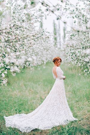 A young woman in a wedding dress is standing in a flowering spring garden. Full-length portrait.
