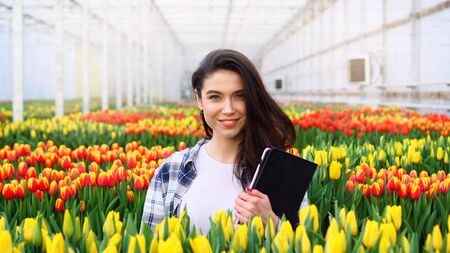 Young smiling female florist is standing with a tablet in her hands in a greenhouse. Close-up. Imagens