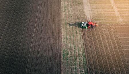 Tractor with a seeder prepares the land for sowing grain crops in ploughed field. Aerial view.
