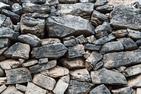 Wall of gray stones of different sizes, close-up.